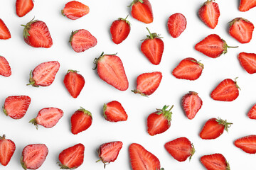 Fototapete - Halves of delicious ripe strawberries on white background, flat lay