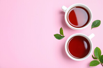 Cups of aromatic black tea and green leaves on pink background, flat lay. Space for text