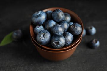 Fototapete - Fresh ripe blueberries in bowl on dark table, closeup