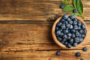 Fototapete - Fresh ripe blueberries in bowl on wooden table, flat lay. Space for text
