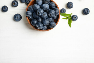 Fototapete - Fresh ripe blueberries in bowl on white wooden table, flat lay. Space for text