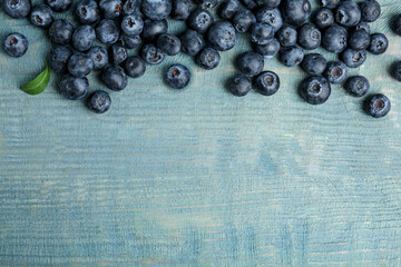Fototapete - Fresh ripe blueberries on wooden table, flat lay. Space for text