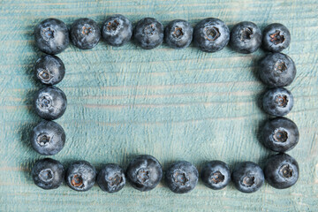Fototapete - Frame of fresh ripe blueberries on wooden table, flat lay. Space for text
