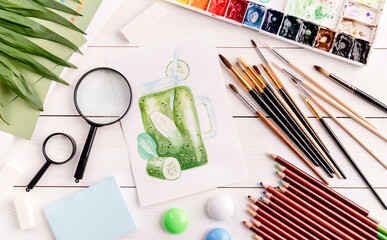 Top view of artist workspace with a smoothie sketch, paintbrushes, magnifying glass and watercolor on white wooden background