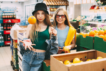 Two blond teenage girls in hipster clothes, stylish glasses and a cap in a store with bright orange