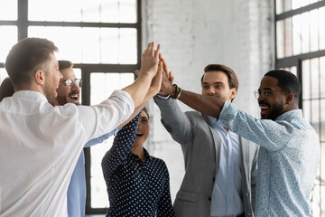 Multi racial millennial affiliates join hands giving high five celebrating common business success...