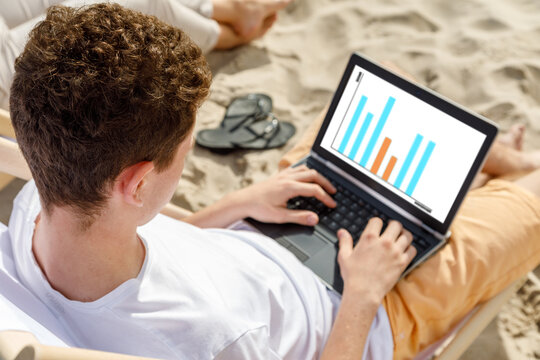 Young man using laptop on beach