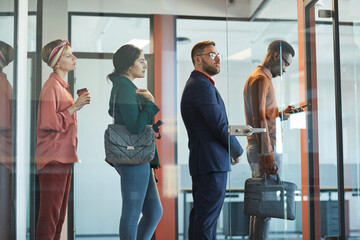 Side view at multi-ethnic group of business people standing in line in office behind glass wall, copy space