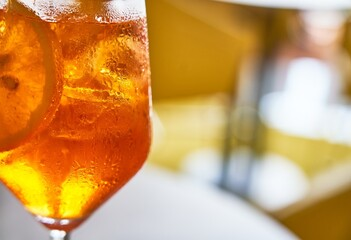 Glass of cold refreshing aperol spritz cocktail on table in summer.
