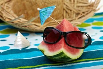 A half watermelon, straw hat, sunglasses, towel.