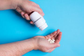 Homem despejando comprimidos de Ivermectina sobre a outra mão com fundo azul claro