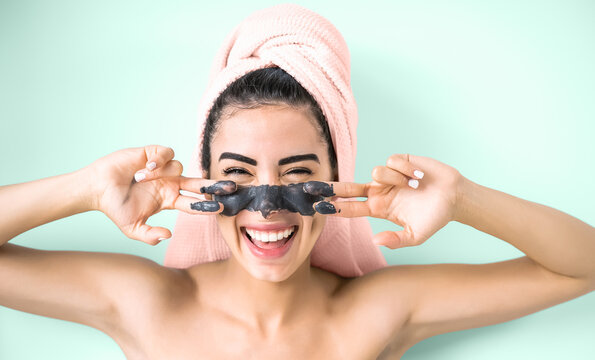 Happy smiling girl applying facial charcoal mask portrait - Young woman having skin care cleanser spa day - Healthy beauty clean treatment and cosmetology products concept - Aquamarine background