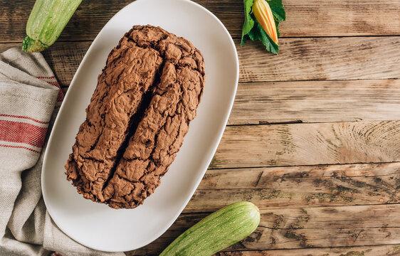 Vegan crunchy chocolate zucchini cake on rustic wooden. Healthy gluten free food.