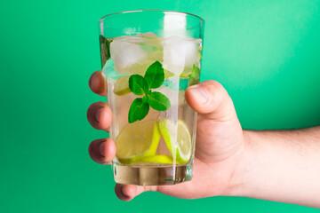 Homem branco segurando um copo de limonada fresca com pedaços de limão e manjericão sobre o fundo verde