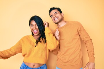 Beautiful latin young couple wearing casual clothes together dancing happy and cheerful, smiling...