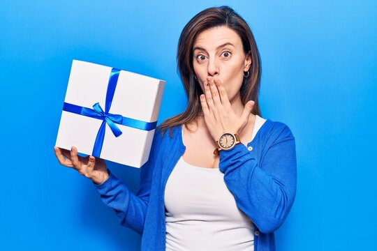 Young beautiful woman holding gift covering mouth with hand, shocked and afraid for mistake. surprised expression
