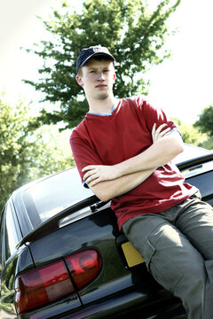 A boy with cap leaning against a car