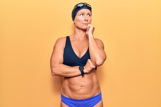 Middle age caucasian blonde woman wearing bikini,  swimming cap and diving googles serious face thinking about question with hand on chin, thoughtful about confusing idea