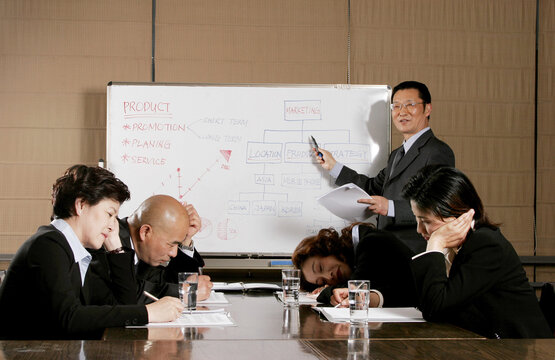 Man and women falling asleep after listening to a dull presentation by the manager