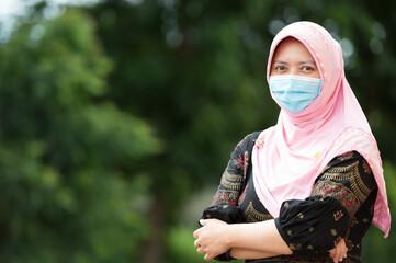 portrait Muslim woman wearing mask, look at camera with pleasure