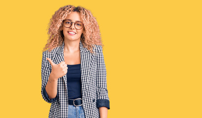 Young blonde woman with curly hair wearing business jacket and glasses doing happy thumbs up gesture with hand. approving expression looking at the camera showing success.