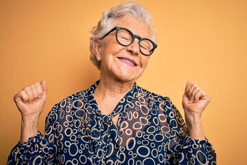 Senior beautiful grey-haired woman wearing casual shirt and glasses over yellow background very happy and excited doing winner gesture with arms raised, smiling and screaming for success. Celebration.