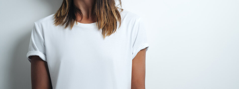 woman in white blank t-shirt, empty wall, horizontal studio close-up. Wide screen, panoramic