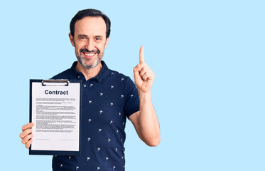 Middle age handsome man holding clipboard with contract document surprised with an idea or question pointing finger with happy face, number one