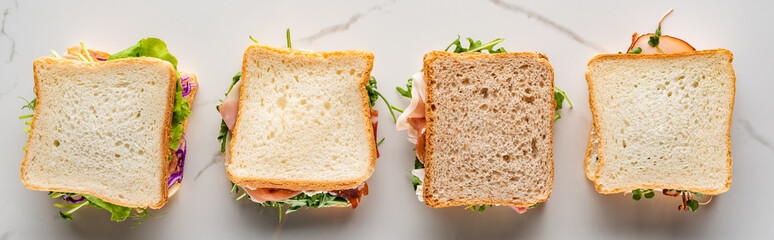 top view of fresh sandwiches on marble white surface, panoramic shot