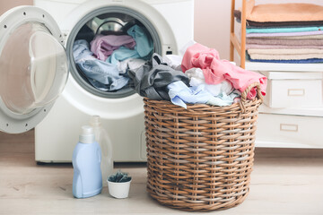 Obraz Washing machine and basket with dirty clothes in home laundry room - fototapety do salonu