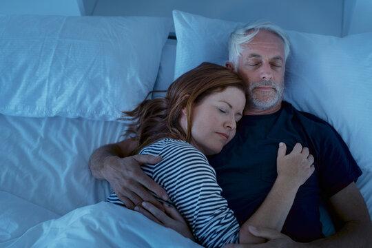 Mature couple sleeping at night