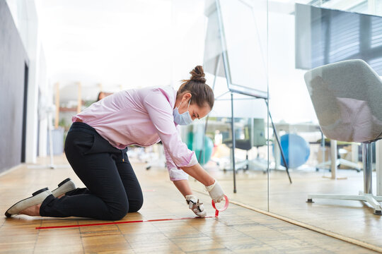 Woman marks floor with tape for keeping distance in the office