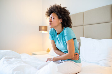 Young woman suffering from abdominal pain while sitting on bed at home. Woman sitting on bed and having stomach ache. Young woman suffering from abdominal pain