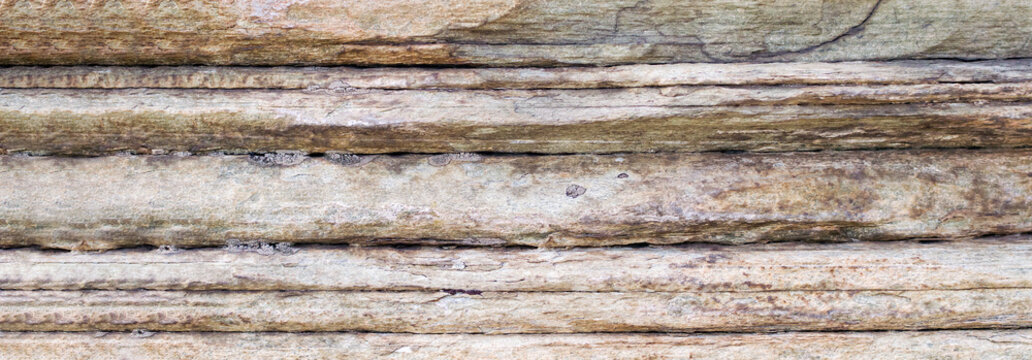 Relief of large gray rock, multi-storey layered rough sedimentary rocks. Natural big stone background, close up texture of layers of horizontal stone surface. Banner with copy space.