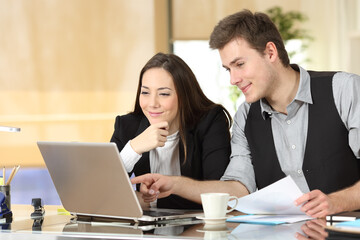 Satisfied office workers checking laptop content