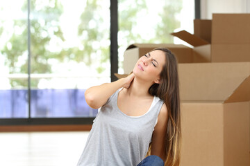 Woman suffering neckache moving home with boxes