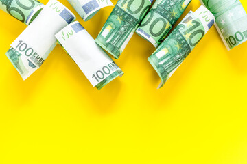 A lot of euro banknote on yellow background top view