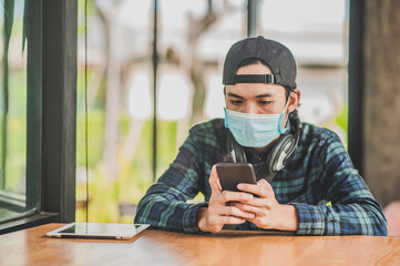 New normal Asian man use face mask listening music by tablet mobile internet