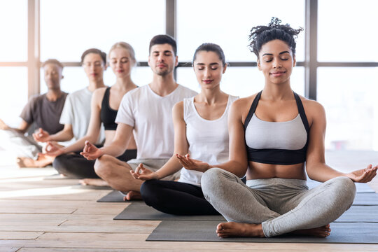 Yoga Class. Group Of Young Sporty People Meditating With Closed Eyes