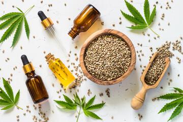 Cannabis oil and cannabis seeds at white.