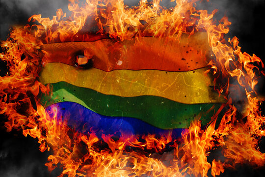 Concept of LGBT tolerance. Burning rainbow flag of LGBT on fire flames background. Blackened charred edges of symbolic flag
