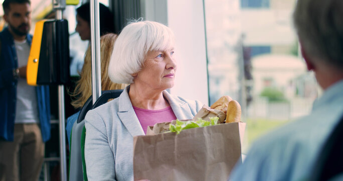 Portrait of the pretty gray-haired Caucasian old woman with a big packet of vegetables and other food going home in the tram from the supermarket or market and looking at the window.