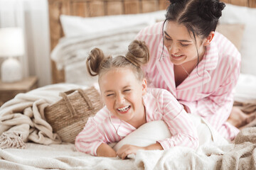 Young active mother and her little daughter having fun together at home in the bedroom wearing pajamas