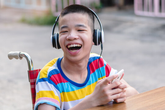 Special need child on wheelchair wear headphones use smartphone and smile face,Study and Work at home for safety from covid 19,Life in the education age of special need kid,Happy disabled boy concept.
