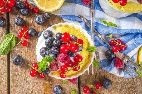 Lemon Mug Cake. Summer sweet dessert in  Microwave. Lemon Mug Pies with fresh berries and whipped cream, on wooden background