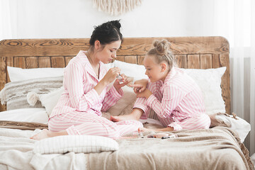 Mother and little daughter having fun together. Mom and her little girl make up