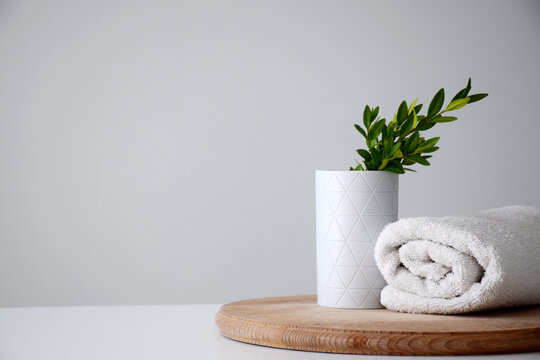 White container and green herb, white rolled towel on wooden board. Spa or beauty care concept. Copy space.