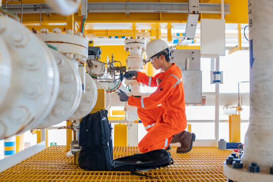 Electrical and Instrument technician repair a solenoid valve at offshore oil and gas central processing platform for maintenance the process equipment.
