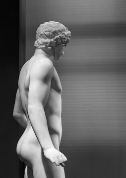 Black and white photo showing the back of marble sculpture of young and handsome naked man