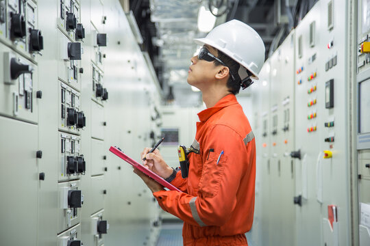 Electrician reading and recording the voltage current and power of electrical power distribution board in switch gear room for maintenance and performance monitor.